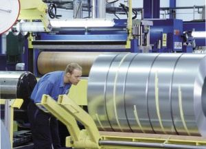 Man placing coils on pallet. årsredovisning; Annual report 1999