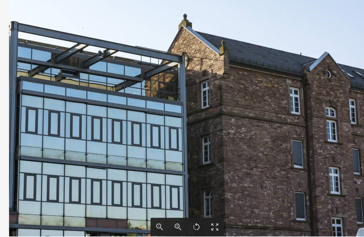 Gammel bygning ved siden af ny og moderne bygning